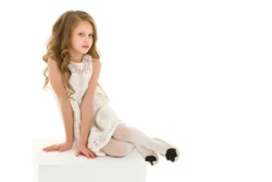 Portrait of Adorable Blonde Girl in Stylish Clothes Sitting