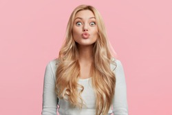 Portrait of adorable blonde woman pouts lips and foolishes alone, makes grimace, rounds lips for making kiss, isolated over pink background. Facial expressions, human emotions and beauty concept