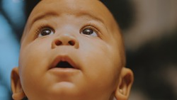 Portrait of adorable curious multiracial dark skin baby looking up. . High quality photo