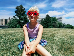 Portrait of adorable cute blonde Caucasian preschool girl wearing funny Canadian maple leaves sunglasses celebrating Canada Day holiday outdoor. Authentic childhood lifestyle. Kid having fun.