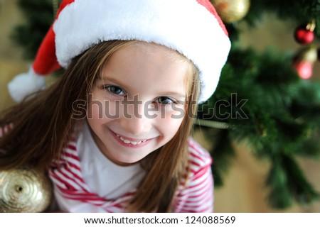 portrait of adorable happy christmas child in santa hat closeup