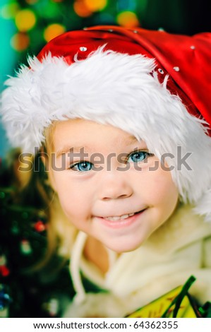 portrait of adorable happy christmas child in santa hat closeup - stock photo