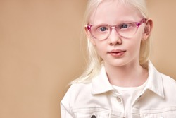 portrait of adorable kid girl albino, beautiful girl in eyeglasses has absolutely white hair color and blue eyes, isolated beige background