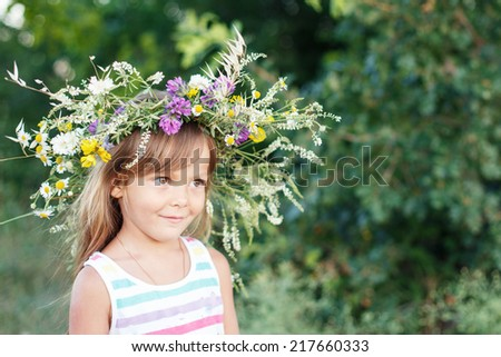 Portrait of adorable kid girl with flower wreath outdoor in the garden #217660333