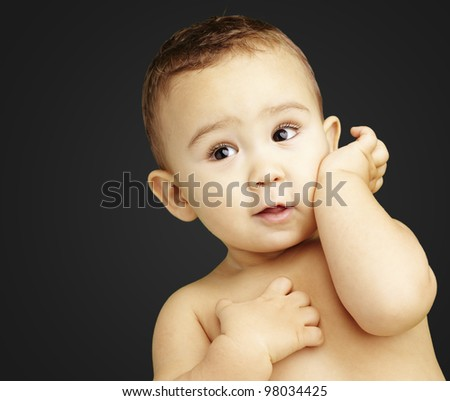 portrait of adorable kid posing over black background