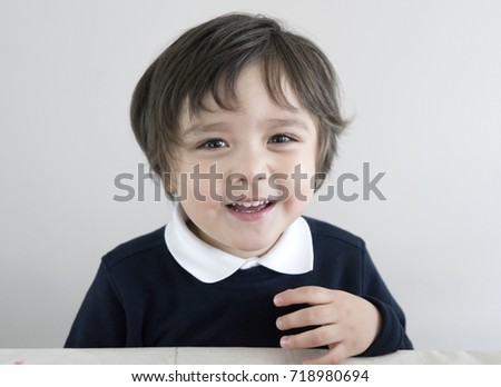 Portrait of adorable kid wearing school uniform looking at camera with a big smiling face, Happy little boy sitting and enjoying his snack time at school, Healthy children concept #718980694