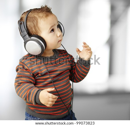 portrait of adorable kid with headphones listening to music indoor