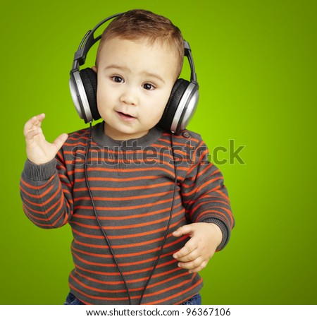 portrait of adorable kid with headphones listening to music over green