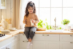 Portrait Of Adorable Little Arab Girl Eating Cookies And Drinking Milk In Kitchen, Cute Female Child Enjoying Healthy Snack At Home, Preschool Kid Sitting At Table And Smiling At Camera, Copy Space
