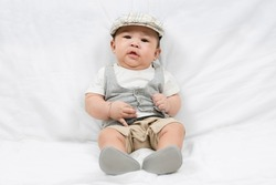 portrait of adorable little baby boy on white wall background. Innocence and babyhood. Fashion kid clothes.