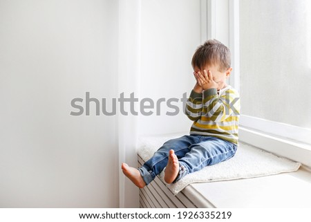 Portrait of adorable little boy sitting on the windowsill and crying. Upset child covering his face at home. Barefoot kid hiding behind palms of his hands. Close up, copy space, background. ストックフォト ©