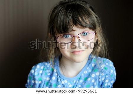 Portrait of adorable little brunette girl in spectacles on dark background