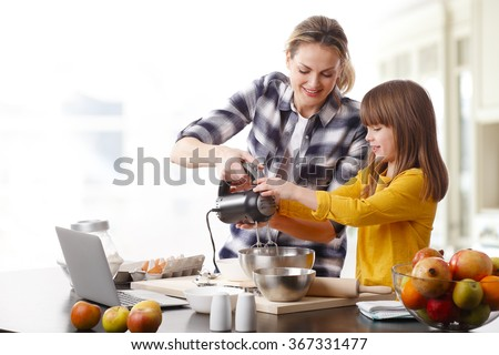Portrait of adorable little girl and her mother baking together at home. Happy mom and her cutie daughter using kitchen robot while mixing the ingredients.