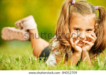 Portrait of adorable little girl lying on grass and propping up her face at summer green park.