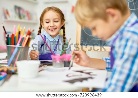 Portrait of adorable little girl smiling happily while enjoying art and craft lesson in pre school working together with boy