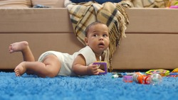 Portrait of adorable mixed race baby lying on blue carpet and holding toy. Cute infant boy or girl on carpet in living room playing with toys. Childhood and family concept