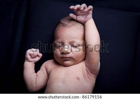 portrait of adorable newborn baby girl on black background