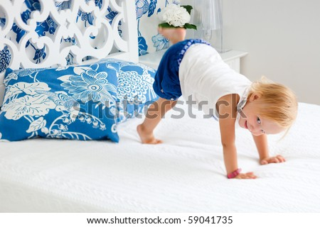 Portrait of adorable playful toddler girl jumping on bed in nicely decorated bedroom