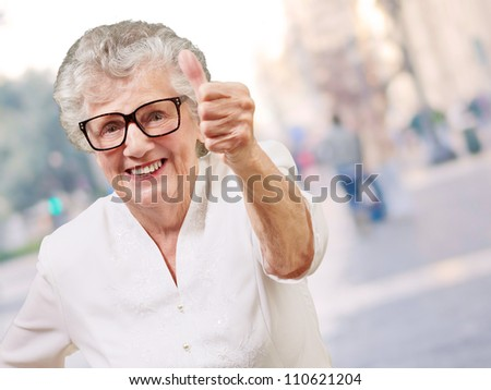 portrait of adorable senior woman doing good gesture at city