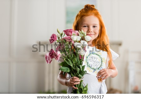 portrait of adorable smiling girl holding bouquet of flowers and happy mothers day greeting card #696596317