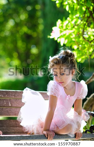 Portrait of adorable toddler girl wearing ballet costume in beautiful garden background