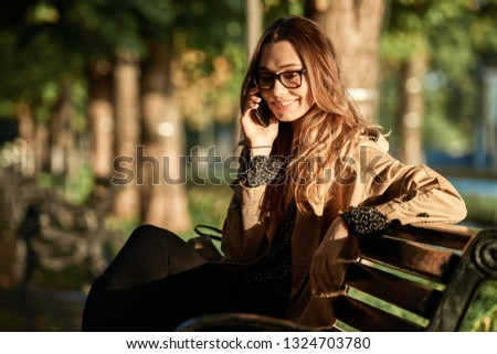 Portrait of adorable woman 20s wearing coat and eyeglasses talking on smartphone while sitting on bench in sunlit alley