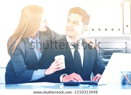 Portrait of adult business couple flirting at table at workplace in office