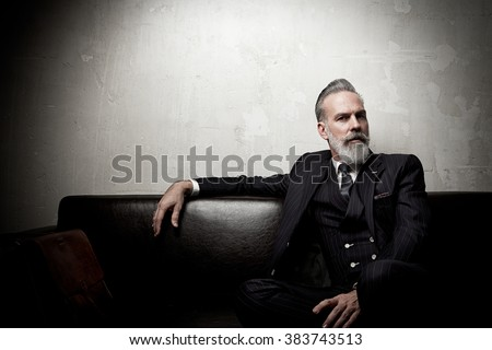 Portrait of adult businessman wearing trendy suit and sitting modern studio on leather sofa against the empty concrete wall. Horizontal, space for ad