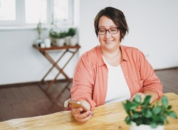Portrait of adult charming brunette woman businesswoman in glasses plus size body positive using mobile at home office