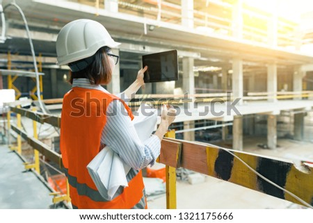 Portrait of adult female builder, engineer, architect, inspector, manager at construction site. Woman makes photo of building.