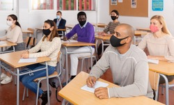 Portrait of adult hispanic man in protective face mask during lesson in extension school. Concept of necessary precautions in COVID pandemic