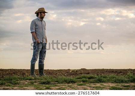 Portrait of Adult Male Farmer Standing on Fertile Agricultural Farm Land Soil Looking into Distance