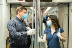 Portrait of adult man and woman in medical face masks and latex gloves chatting friendly in modern subway car. Use of public transport and people communication in context of COVID 19 pandemic