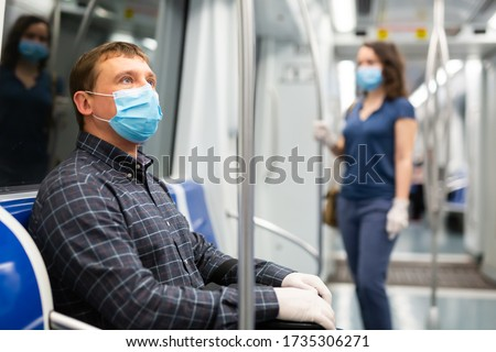 Portrait of adult man in disposable mask and gloves traveling in subway train during daily commute to work in spring day. Concept of precautions during public transport use in COVID 19 pandemic