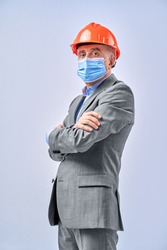 Portrait of adult of architect in hardhat and face mask posing in studio, isolated on blue background. Protection and safety concept