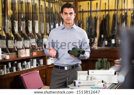 Portrait of adult salesman proposing hunting equipments in specialized shop