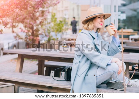 Portrait of adult stylish woman in stylish hat and coat holding tasty coffee to go in hand and smiling at camera in leisure time in urban setting.Positive hipster girl resting with caffeine beverage