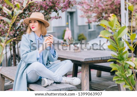 Portrait of adult stylish woman in stylish hat and coat holding tasty coffee to go in hand and smiling at camera in leisure time in urban setting.Positive hipster girl resting with caffeine beverage #1399063907