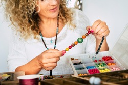Portrait of adult woman creating beads bracelets and necklace at home for new modern and trendy business - people spent time at home doing hobby or alternative job concept