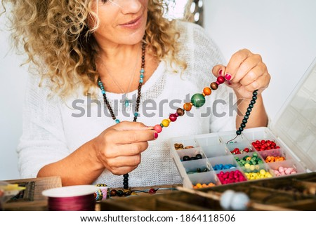 Portrait of adult woman creating beads bracelets and necklace at home for new modern and trendy business - people spent time at home doing hobby or alternative job concept Foto d'archivio ©