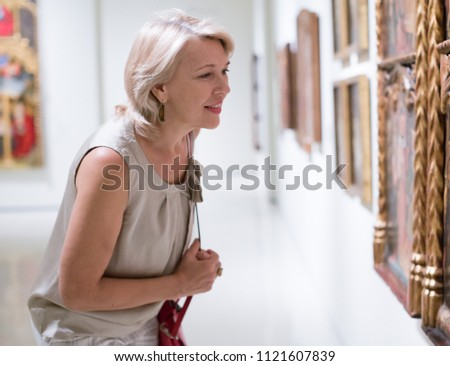 Portrait of adult woman near picture collection in the museum