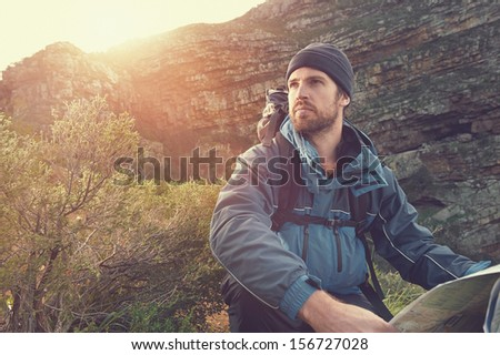 Shutterstock portrait of adventure man with map and extreme explorer gear on mountain with sunrise or sunset