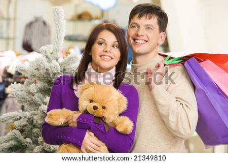 Portrait of affectionate couple looking for nice presents for Christmas in the mall