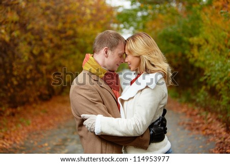 Portrait of affectionate couple standing face to face in autumnal park