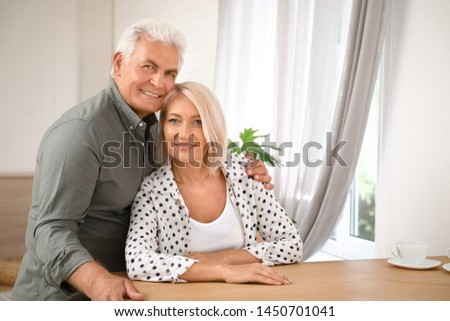 Portrait of affectionate senior couple at home. Space for text