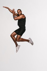 Portrait of african american athlete jumping in air. Fit man doing exercise on white background.
