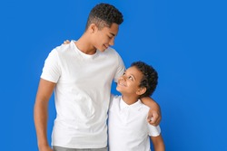 Portrait of African-American brothers on color background
