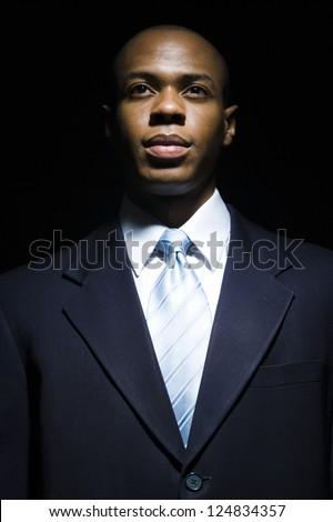 Portrait of African American businessman in darkness