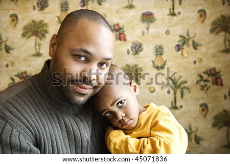 Portrait of african american father holding his young son and looking at viewer.  Horizontal shot.