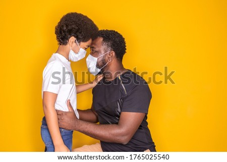 Portrait of  African American father with toddler son using mask. Father and son wearing mask to protect covid 19, quarantine. Stay at home concept. Fathers day!